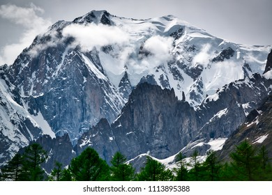 Glacier of Mont Blanc seen from the Ferret Valley in spring season with clouds on the summit and trees in foreground, Aosta Valley - Italy