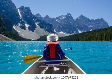 With Glacier and mountain background, woman wearing colorful hat, life vest and coat guides canoe on the uniquely blue water of Moraine Lake, Alberta, Canada
