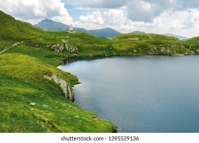 glacier mountain lake in summer. beautiful nature scenery in romania. wonderful background with water, grass, and rocks. location fagaras ridge