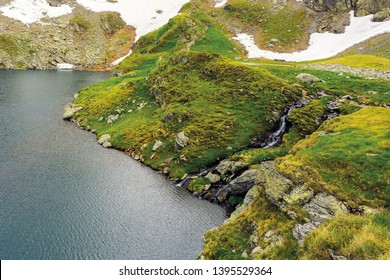 glacier mountain lake in summer. beautiful nature scenery. wonderful background with water, grass, and rocks