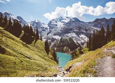 Glacier pond Oeschinensee. Popular tourist attraction. Picturesque and gorgeous scene. Location Swiss alps, Kandersteg, Bernese Oberland, Europe. Vintage effect. Instagram filtered. Beauty world.