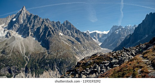 A glacier valley in the region of Chamonix in the alps of France. High alpine snow covered mountains surround the foreground rocks and alpine terrain.