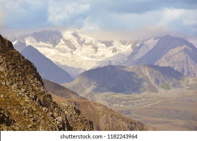 The glaciers of the Aletschhorn in the Bernese Alps viewed from the South under cloudy skies from the Italian Swiss border