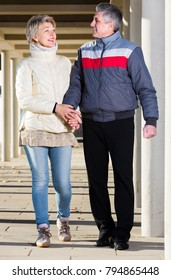 Glad adult husband and wife are walking together clear sunny day between columns