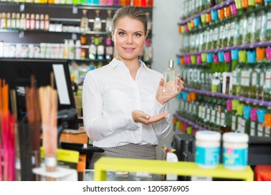 glad adult saleswoman offering new fragrance in perfume shop