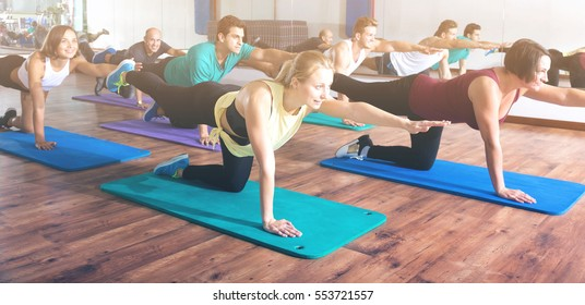 Glad adults having yoga class in sport club