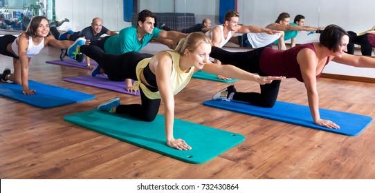 Glad adults having yoga class in sport club
