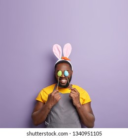 Glad African American man covers eyes with two Easter eggs, wears bunny ears, wears apron, prepares delicious traditional dish for holiday, models over violet wall with free space for promotion