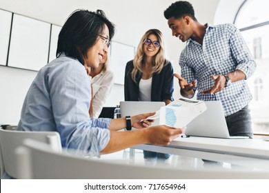 Glad asian guy in blue shirt holding documents and smiling while his colleagues joking on background. Indoor portrait of young international co-workers spending time together in office.
