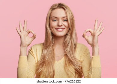 Glad attractive woman shows ok sign as expresses approval, gestures in studio against pink background, has cheerful expression. Photo of beautiful female has appealing appearance, being optimstic