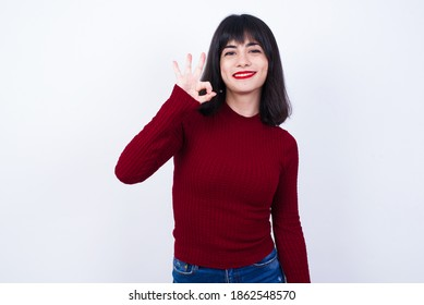 Glad attractive Young Caucasian beautiful woman wearing red T-shirt against white background shows ok sign with hand as expresses approval, has cheerful expression, being optimistic.