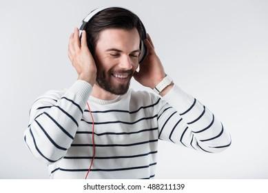 Glad bearded man listening to music.