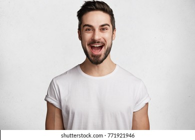 Glad bearded young male happy to have date with girlfriend, being in hgh temper or good mood, dressed casually, isolated over white studio background. Shot of excited unshaven happy man indoor