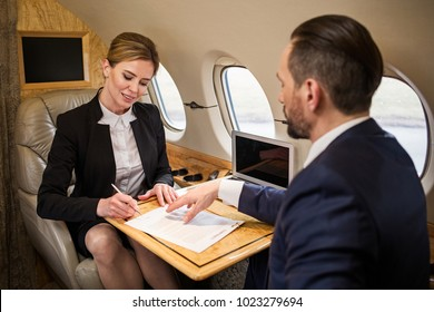 Glad beautiful woman in plane cabin signing contract, her colleague is sitting in front of her. Focus on lady