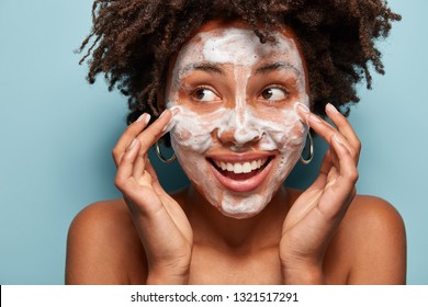 Glad black young woman cleans face skin with soap, applies foam, poses topless, looks away with broad smile, touches cheeks, isolated over blue background. Skincare, wellness and hygiene concept