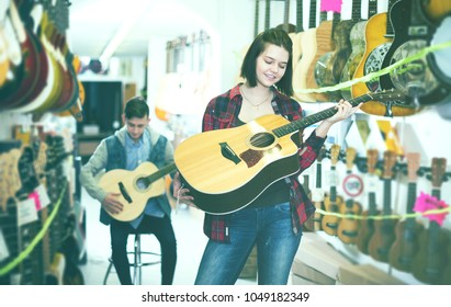 Glad boy and girl choosing best acoustic guitar in guitar shop