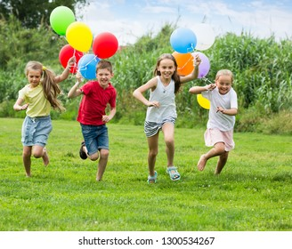 glad boy and girls holding air balloons and running in summer park