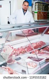 Glad butcher cutting fresh lamb meat in workshop