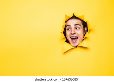 Glad Caucasian man with toothy smile looks positively aside, shows face in paper hole, isolated over yellow background with blank space. Positive emotions. Man peeks through ripped paper