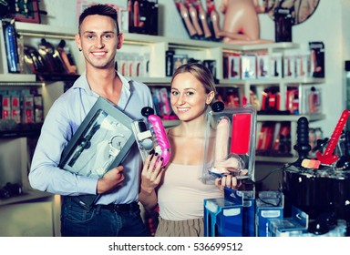 Glad cheerful adult couple buying sex accessories in shop for adults