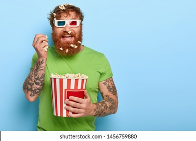 Glad cheerful man has fun, eats popcorn in cinema, enjoys funny movie, good company, wears 3d glasses, green t shirt, has tattooed arm, stands against blue wall with blank space. Fast food in theatre