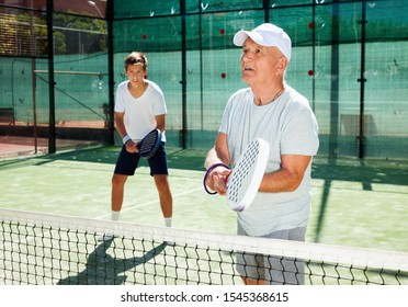 Glad cheerful padel players of different generations playing padel court
