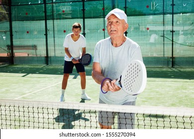 Glad cheerful positive padel players of different generations playing padel court