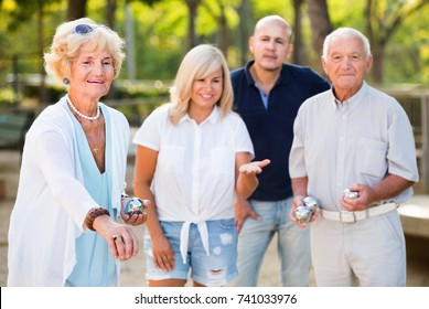 Glad cheerful positive smiling family playing petanque in outdoor