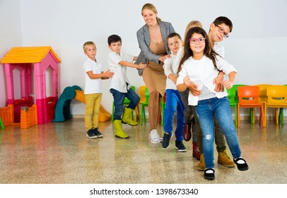 Glad cheerful positive smiling female teacher playing circle game with children in classrom