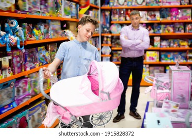 Glad cheerful positive smiling teen boy choosing pink stroller for dolls in children toy store with adult man dazedly looking at him