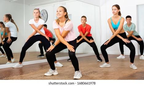 Glad cheerful positive smiling teenage dancers practicing active vigorous dance in modern studio