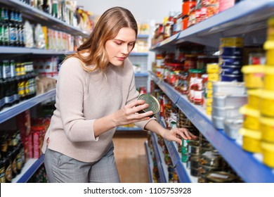 Glad cheerful positive smiling woman customer holding canned fish  goods in the food store