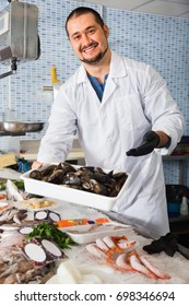 Glad cheerful  seller stands behind counter with fish and holds in hand container with big mussels