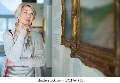 Glad cheerful  smiling female visitor looking at artwork painting in the museum indoors