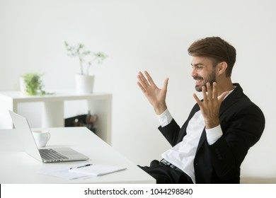 Glad company ceo satisfied with achievement looking at laptop screen, excited businessman in suit motivated by business win feels relieved figuring out online project result watching good news on pc