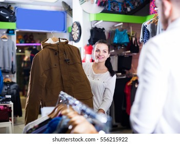 Glad couple choosing new coat in sports store