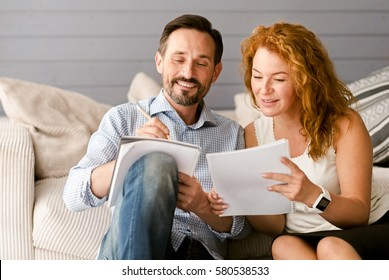 Glad couple enjoying freelance job at home