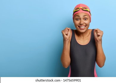 Glad dark skinned healthy swimmer clenches fists, makes triumph gesture, happy to win swimming contest, wears black bikini and diving equipment, stands against blue studio wall, empty space.