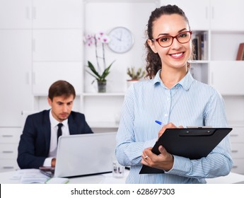 Glad  efficient business female secretary having cardboard in hands and working in office