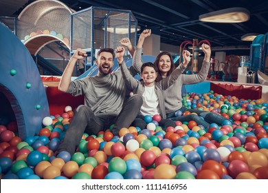 Glad family sitting in pool with balls. Family rest, leisure. Spending holiday together. Entertainment center, mall, amusement park.