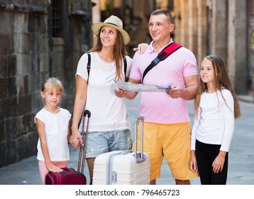 Glad family of tourists with two children looking for destination with city map