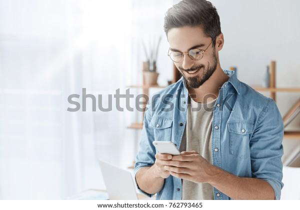 Un joven barbudo de moda lleva ropa elegante y pantalones denim, tiene un moderno peinado, está feliz de intercambiar mensajes con sus amigos, usa conexión gratuita a internet en un moderno gadget electrónico