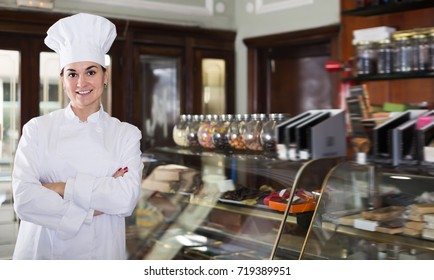Glad female assistant demonstrating assortment of confectionery