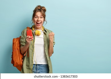 Glad female blogger clenches fist, feels excited from statistics on web page in social networks, uses cell phone and headphones, wears khaki shirt and jeans, carries backpack, isolated on blue wall