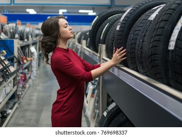 Glad female customer taking new tires in the supermarket for buying. She looks happy. Big shopping mall with car goods.