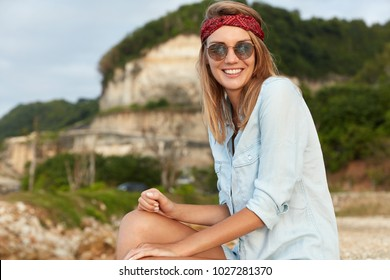 Glad female model in headband and sunglasses sits at top of cliff, being in high spirit, feels freedom and relaxation, admires beautiful views. People, recreation, nature and lifestyle concept