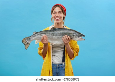 Glad fisher woman in yellow anorak and jeand overalls holding huge fish rejoicing to catch it demonstrating her work while standing over blue background. People, hobby, recreation and fishing