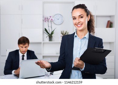 Glad friendly efficient business female secretary having cardboard in hands and working in office