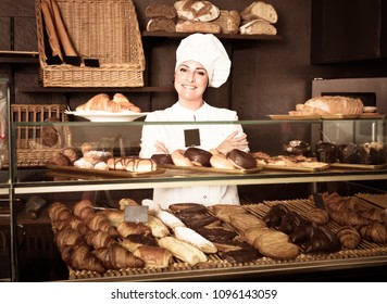 Glad friendly female cooks demonstrating and selling to the customer pastry in the cafe counter