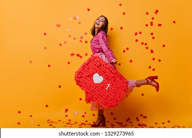 Glad girl in high heel shoes enjoying social networks. Fashionable european woman in pink attire laughing and dancing on yellow background.